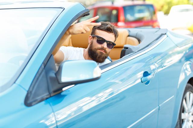 スポーツカーに乗る男